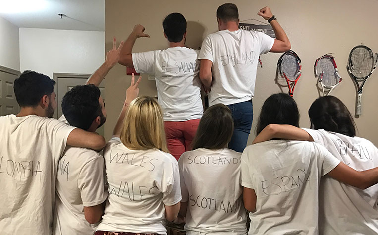 tennis athletes friends from different nationality on their backs with white shirts and the name of their country written on them